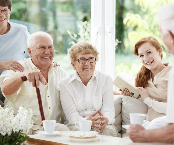 Senior people spends time together with young red-haired caregiver